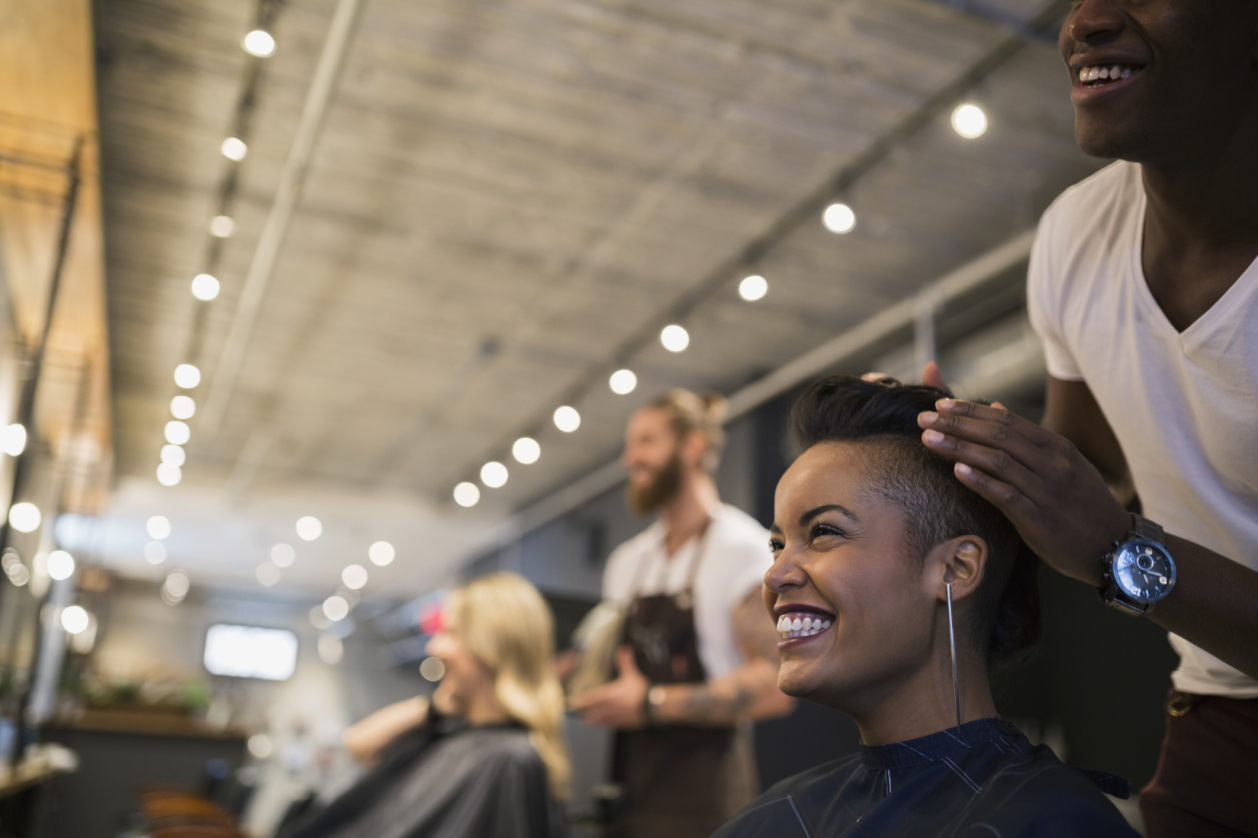 Smiling woman getting hair styled in hair salon